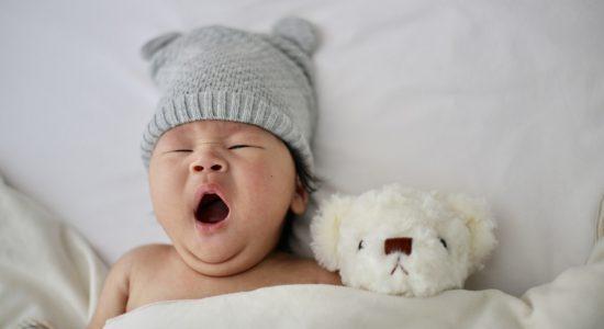 Bébé qui baille couché dans son lit avec sa peluche pour faire la sieste