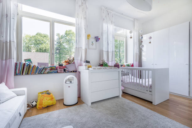 Chambre de bébé fonctionnelle avec lit à barreaux, table à langer, tapis et espace de jeux