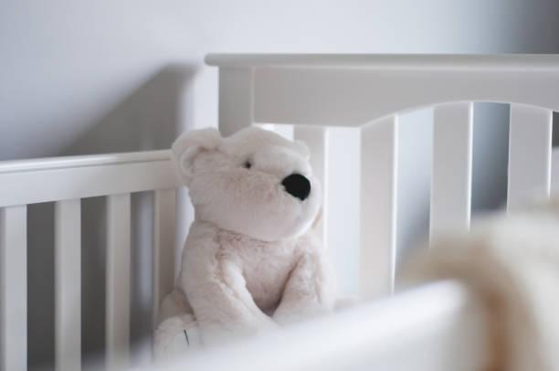 Gros plan sur un ours en peluche blanc dans un lit de bébé