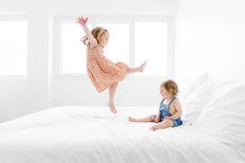 Deux enfants qui sautent sur un lit dans une pièce blanche lumineuse