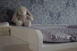 Chambre de bébé avec une table à langer et une peluche lapin